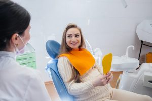 A professional dentist treats and examines the oral cavity of a pregnant girl in a modern dental office. Dentistry