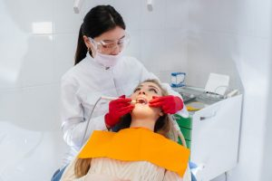 A professional dentist performs treatment and examination of the patient's oral cavity in close-up. Dentistry